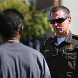 Utah Highway Patrol Sgt. Randy Riches talks with a homeless man during an arrest as law enforcement officials conduct Operation Rio Grande in Salt Lake City on Monday, Aug. 14, 2017.