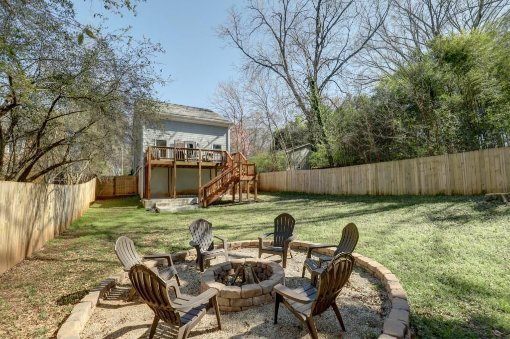Looking at the back of a house with a large deck from the yard with a firepit.