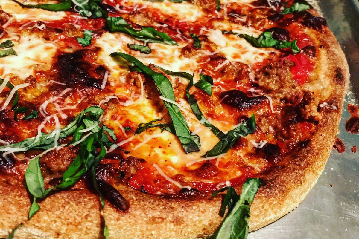 A cheese pizza sprinkled with shredded parmesan cheese and fresh basil from La Calavera in Atlanta