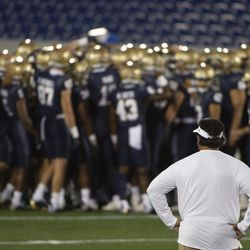 Navy head coach Ken Niumatalolo looks on as his team huddles before an NCAA college football game against BYU, Monday, Sept. 7, 2020, in Annapolis, Md.