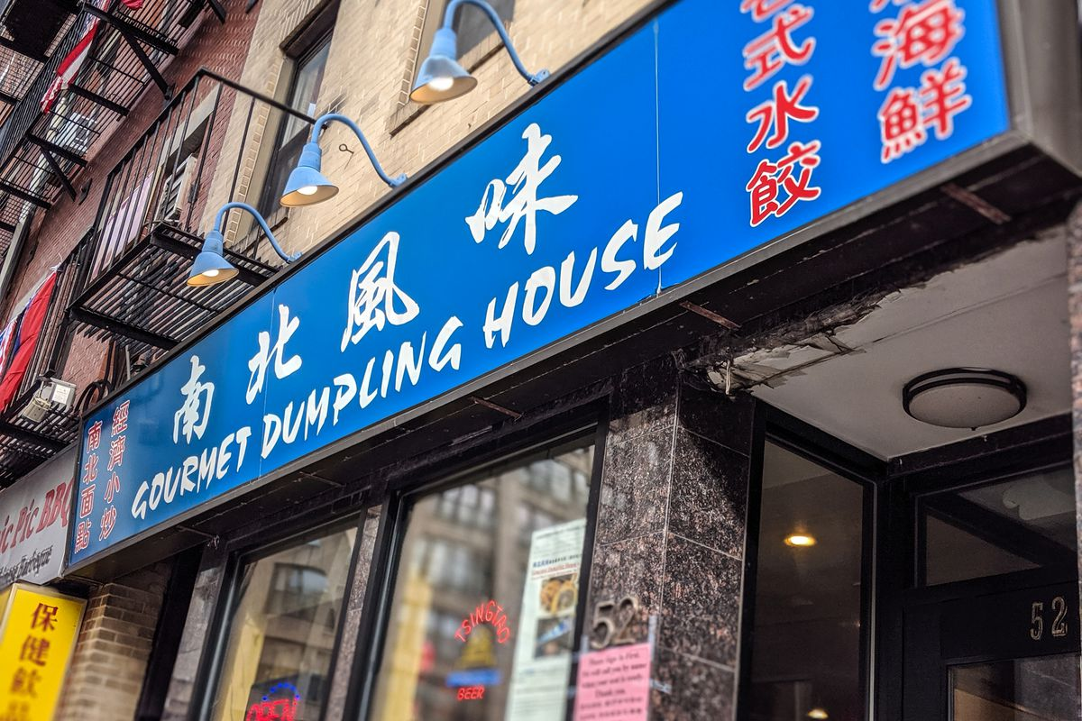 The exterior of Gourmet Dumpling House in Boston's Chinatown, featuring blue signage with white English text and red Chinese text
