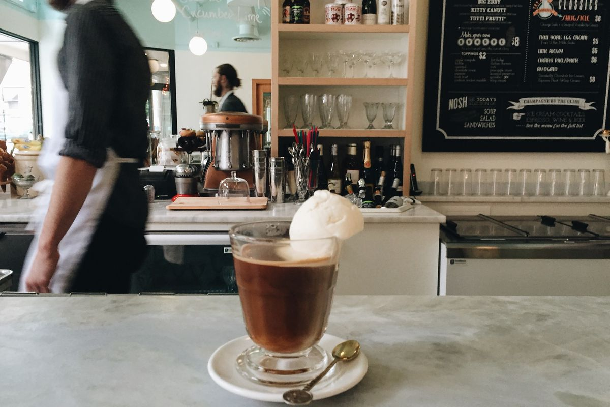 A chocolatey drink with a scoop of ice cream sits on a counter at Shug's Soda Fountain.