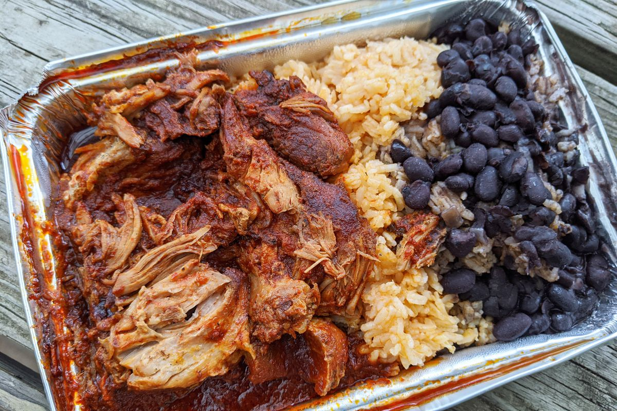An aluminum vessel with pork in red sauce, black beans, and yellow rice