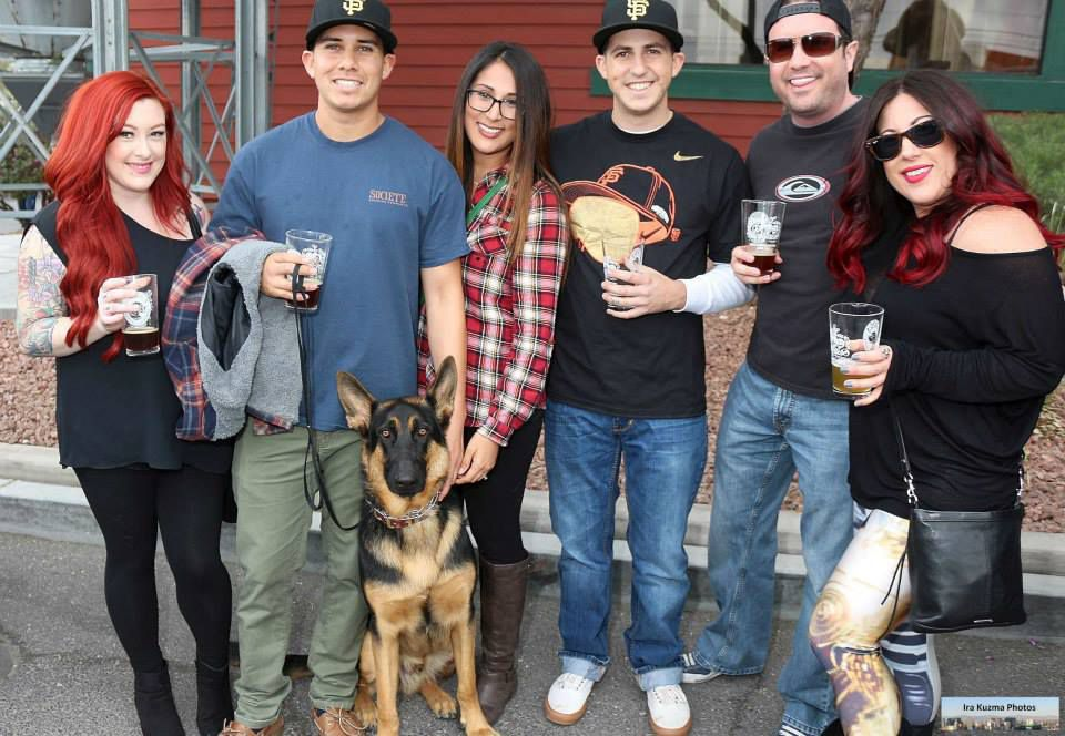 A group of people stand on a patio with a dog.