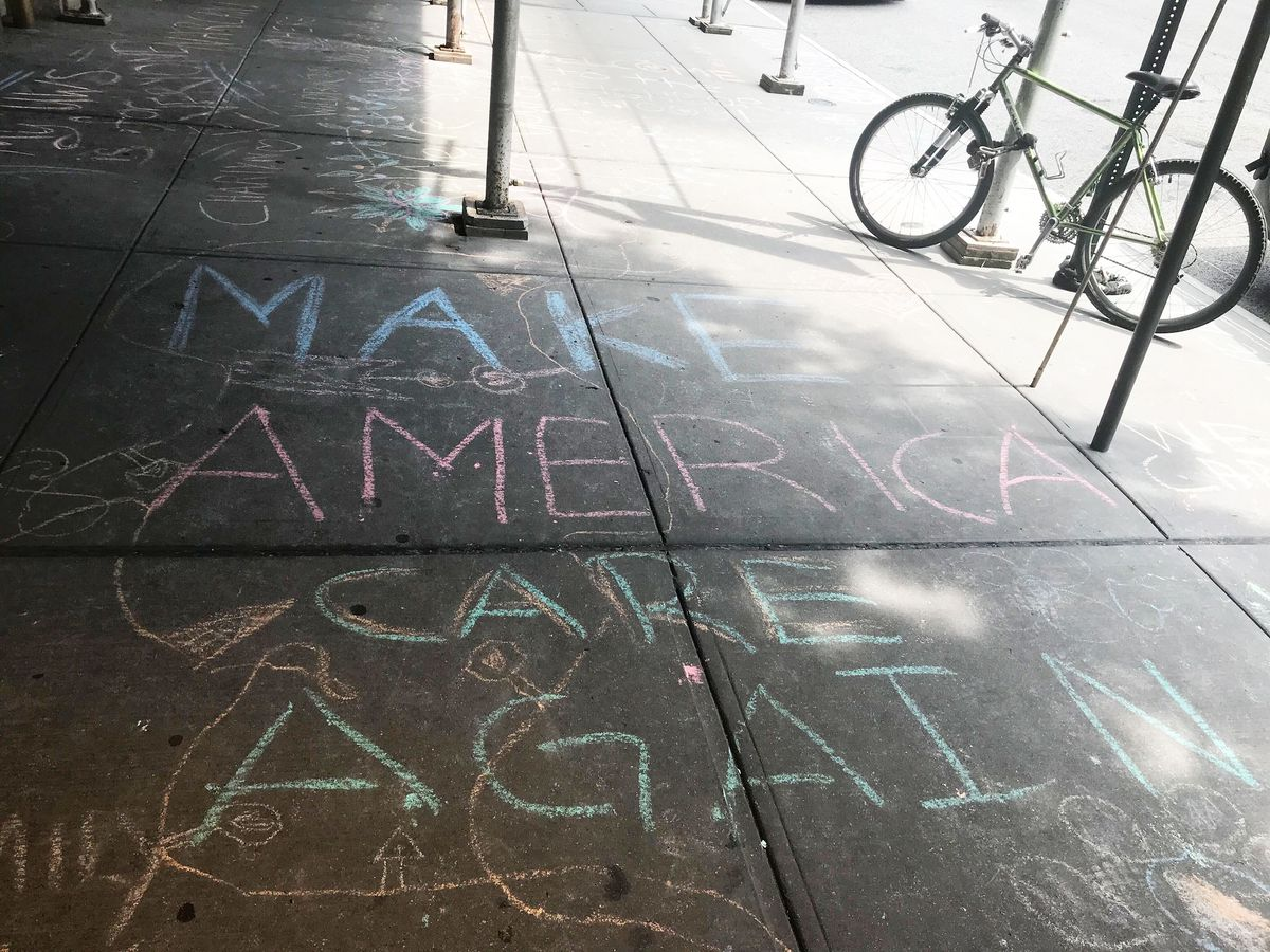 """A message written in chalk on a sidewalk that reads: """"Make America Care Again."""""""