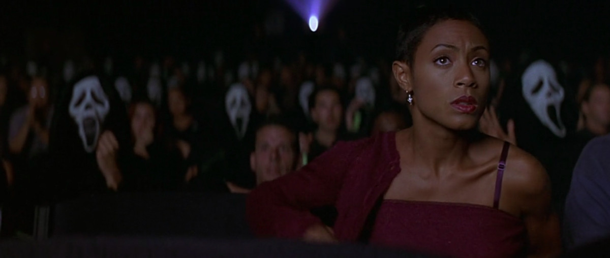 jada pinkett smith in scream 2 putting on her jacket in a movie theater full of ghostface cosplayers