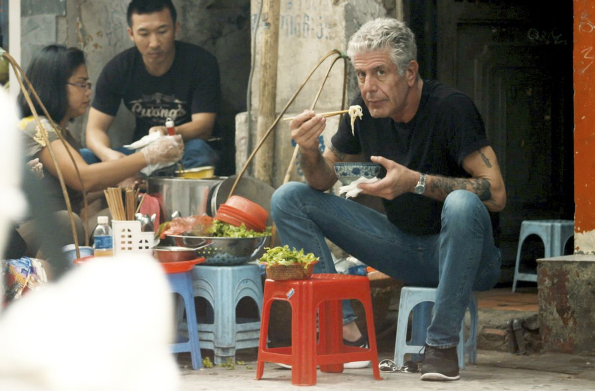 Anthony Bourdain sits on a low stool and eats noodles.