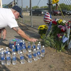 Keith Gustafson, of Prescott, counts out 19 bottles of water he just placed at a memorial in front of Prescott Fire Station #7 on Monday, July 1, 2013. Nineteen firefighters have died in the Yarnell Hill Fire that has ripped through half of the town and sent residents to Prescott for safety. (AP Photo/The Arizona Republic, David Wallace)