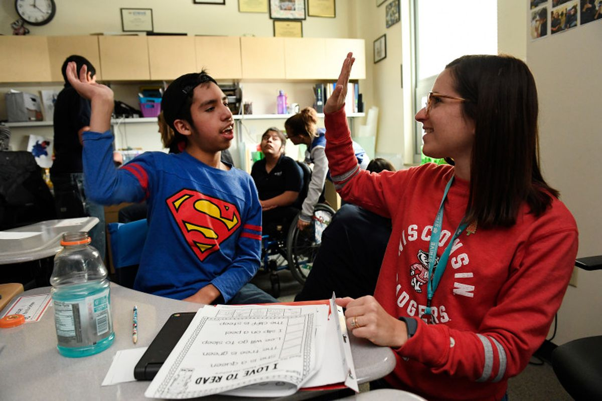 Josue Bonilla, 13, left, gets a high five from his teacher Wendi Sussman, right, after completing a hard reading lesson in his multi-intensive special education class at STRIVE Prep charter school in Denver in 2016.