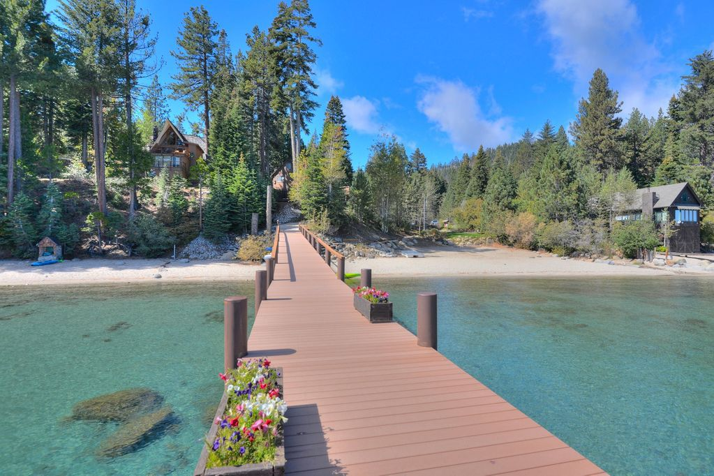 In the foreground is a dock with flowers in planters. The dock is spanning over Lake Tahoe. In the distance are cabins and trees.