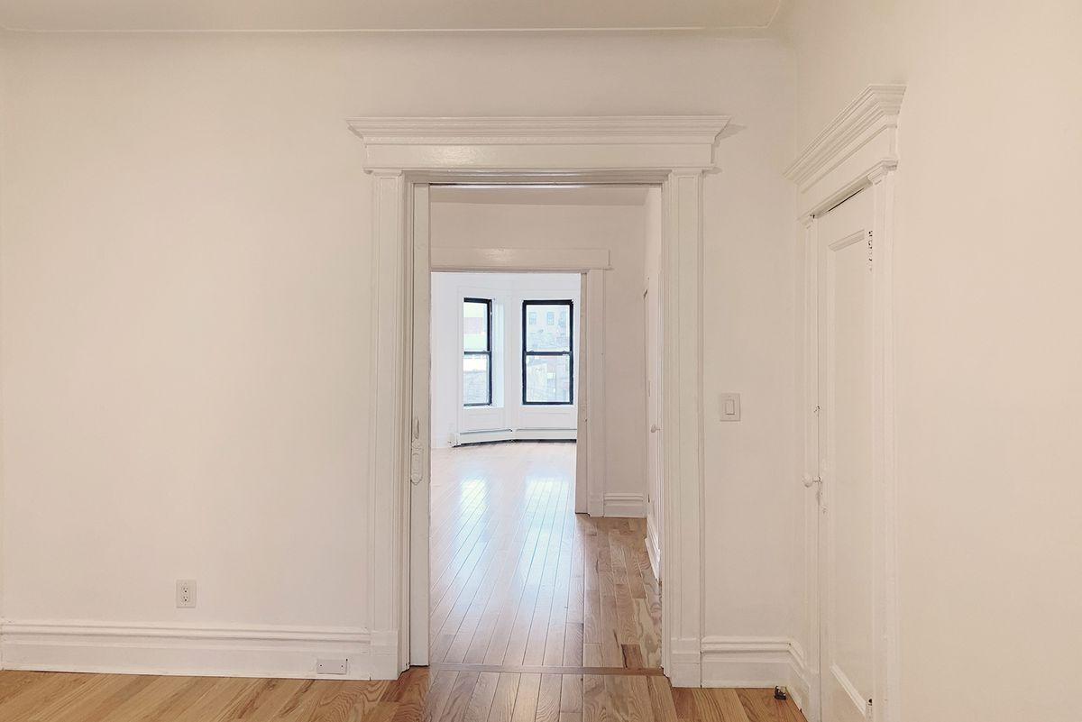 A bedroom with base moldings, white walls, and hardwood floors.