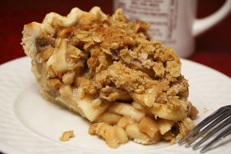 A thick cut piece of apple pie with crumbly crust sits atop a plate with a fork nearby