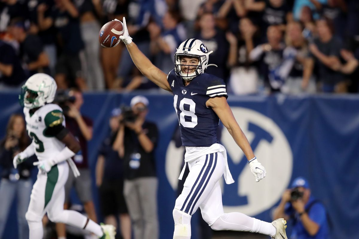 Brigham Young Cougars wide receiver Gunner Romney, wearing a blue jersey and white helmet, celebrates after making a long catch for a touchdown