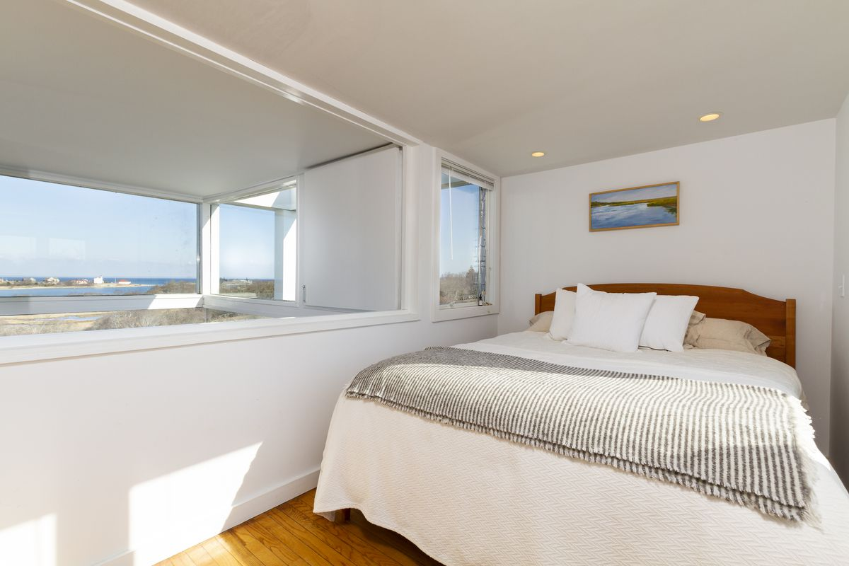 A bed sits in a narrow room with a gray blanket and white comforters. There is a large boxy window on the left.