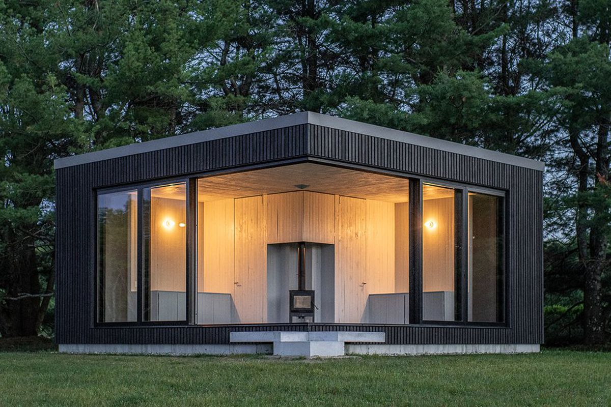 This symmetrical cabin is clad in charred timber and is fronted by large sliding glass doors that can open the space up to the fields around it. The interior is sparely furnished with a central room that's painted white, with a fireplace at the center and