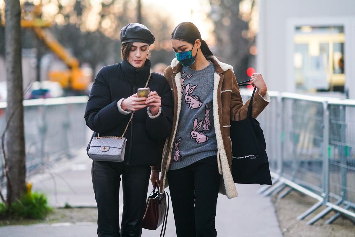 Two people, one masked and one not, walk down a sidewalk, both looking at a phone held by one of them.