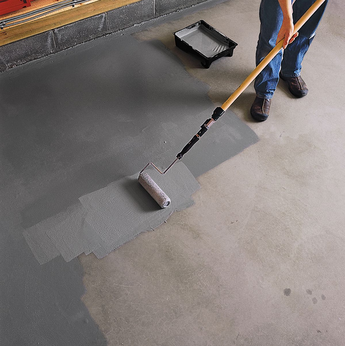 Person using a roller to put epoxy paint onto the garage floor.