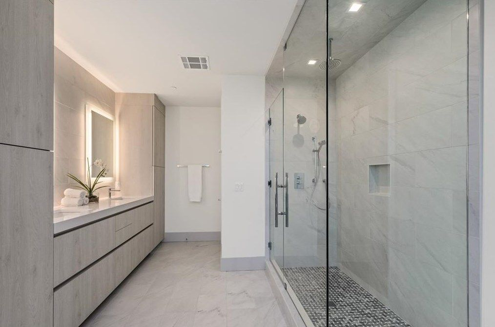 A white master bathroom with a huge shower at right and a sink at left.