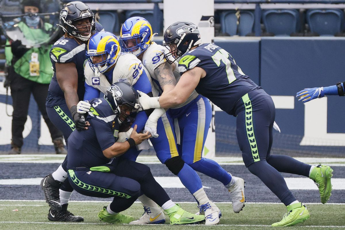 Quarterback Russell Wilson #3 of the Seattle Seahawks is sacked by defensive end Aaron Donald #99 of the Los Angeles Rams during the the NFC Wild Card Playoff game at Lumen Field on January 09, 2021 in Seattle, Washington.