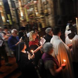 Catholic worshippers attend a procession during Holy Saturday inside the Church of the Holy Sepulchre, traditionally believed to be the burial site of Jesus Christ, in Jerusalem's Old City, Saturday, April 7, 2012. (AP Photo/Bernat Armangue)