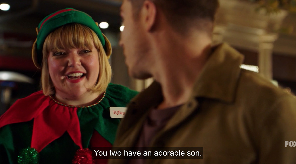 """A woman dressed as an elf telling Buck, """"You two have an adorable son"""""""