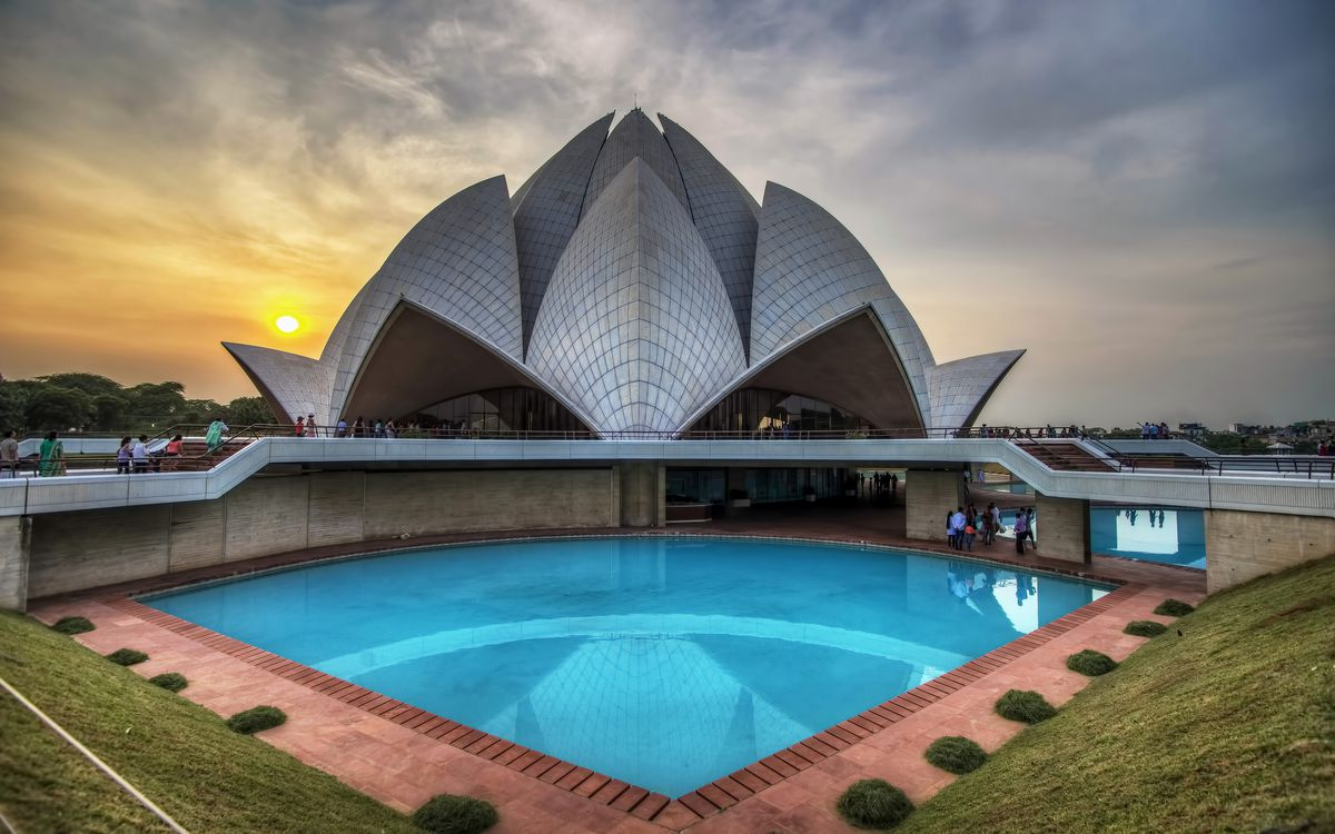 """The exterior of the <span data-author=""""843"""">Bahai Lotus Temple in India. In the foreground is a still water pool. The temple is shaped like a flower.</span>"""