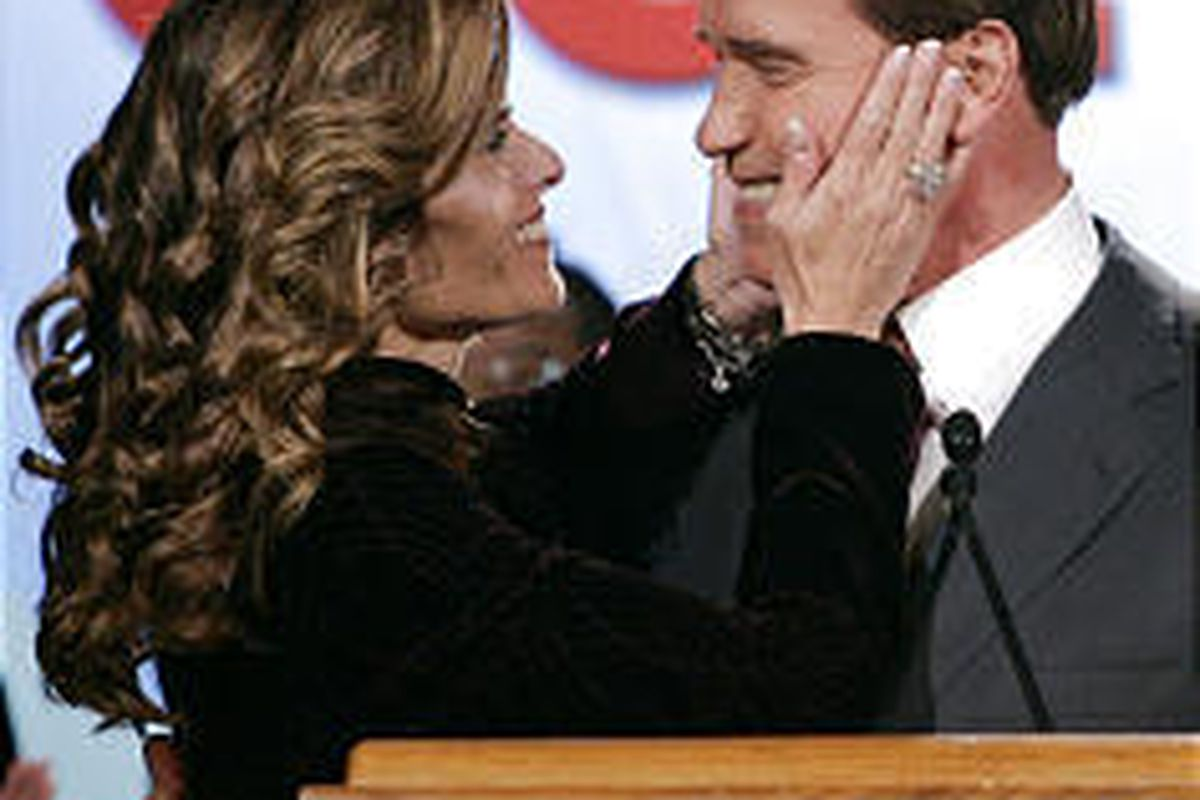 Gov. Arnold Schwarzenegger embraces his wife, Maria Shriver, as he waits Tuesday night for election results on his ballot proposals.