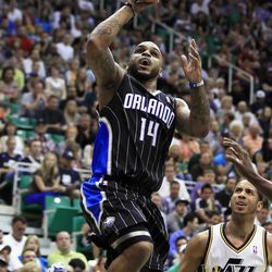 Orlando Magic's Jameer Nelson, left, shoots the ball as Utah Jazz's Devin Harris looks on during the first half of an NBA basketball game in Salt Lake City, Saturday, April 21, 2012.