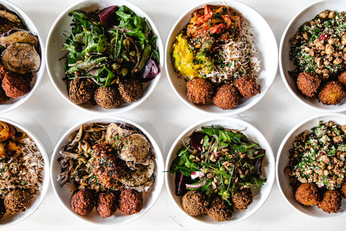 Eight bowls of Mama Sesame falafel sit on a white table, topped with a number of different salads and spreads.