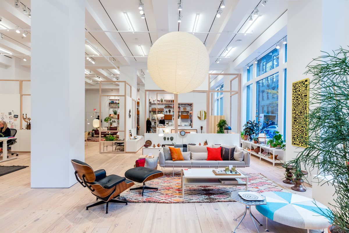 The interior of a store. There are high ceilings, couches, chairs, and other home-goods.