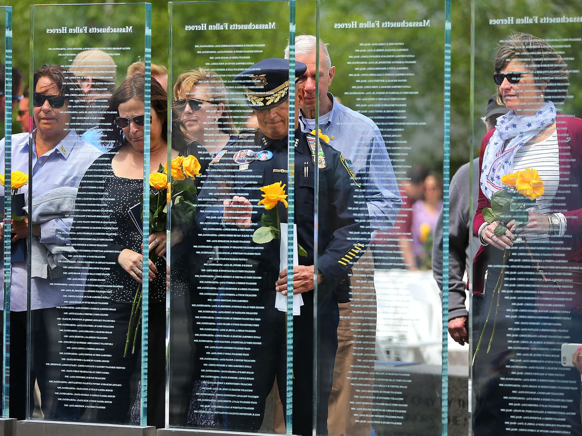 People standing before a transparent glass memorial with names on the glass.