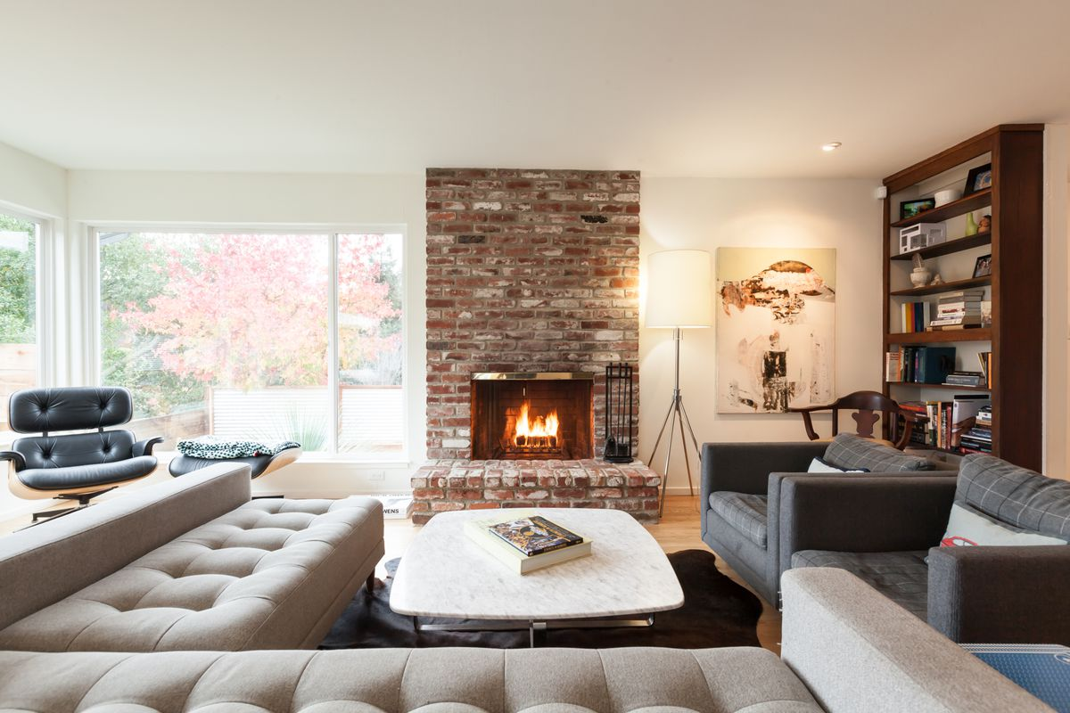 A living area with a fireplace, bookshelf, couch, arm chairs, and floor to ceiling windows.