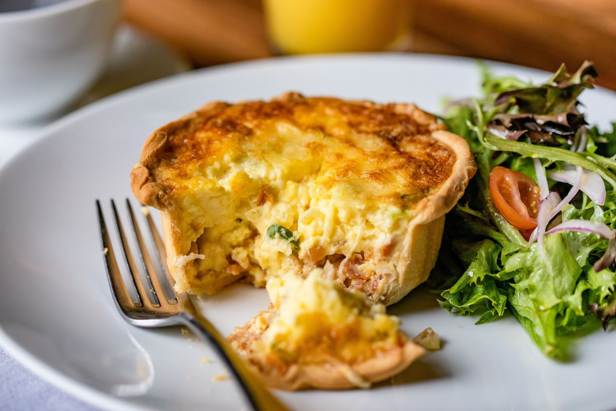 a small quiche on a white plate next to a salad and a fork, with e piece cut out of it