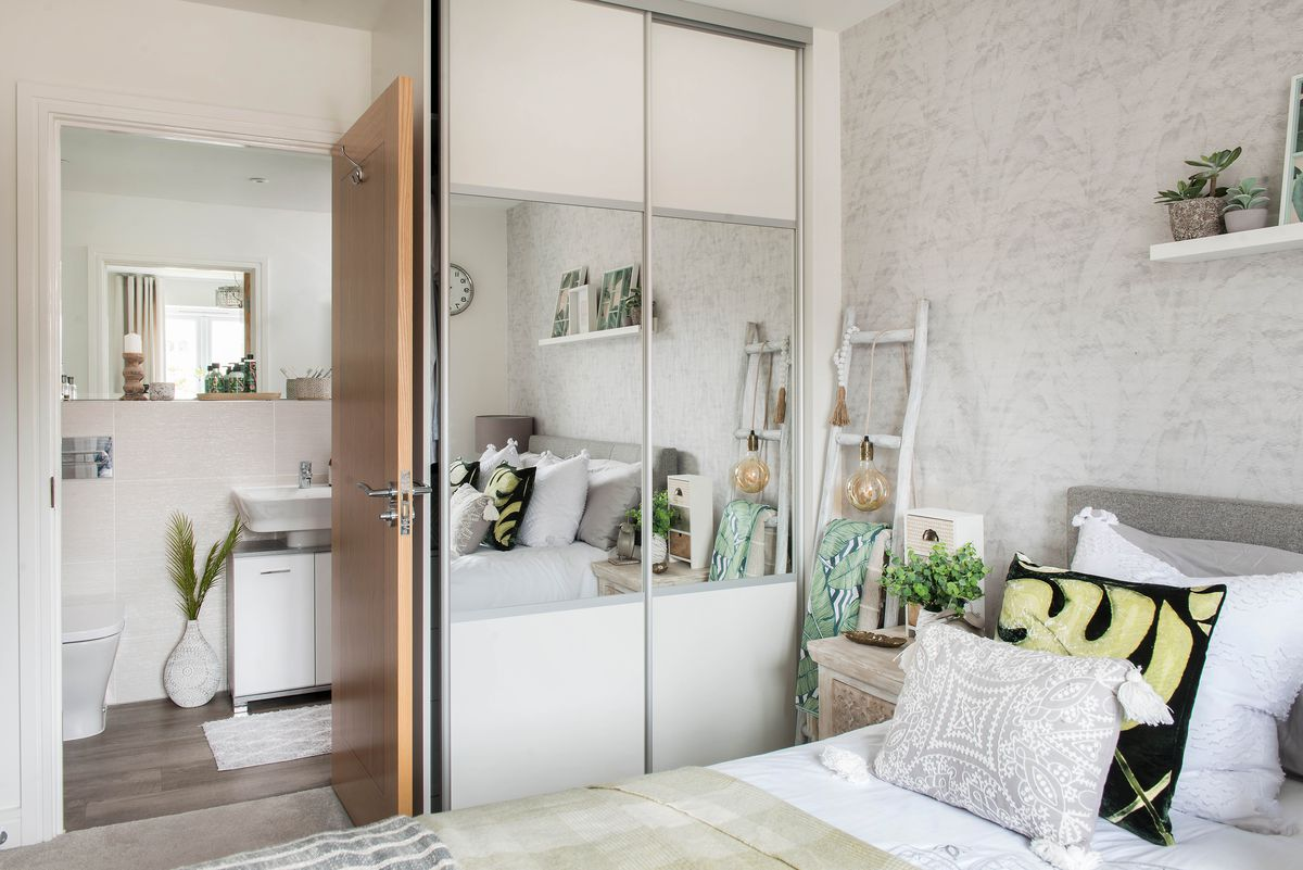 A small modern bedroom with en suite and mirrors on the closet doors.