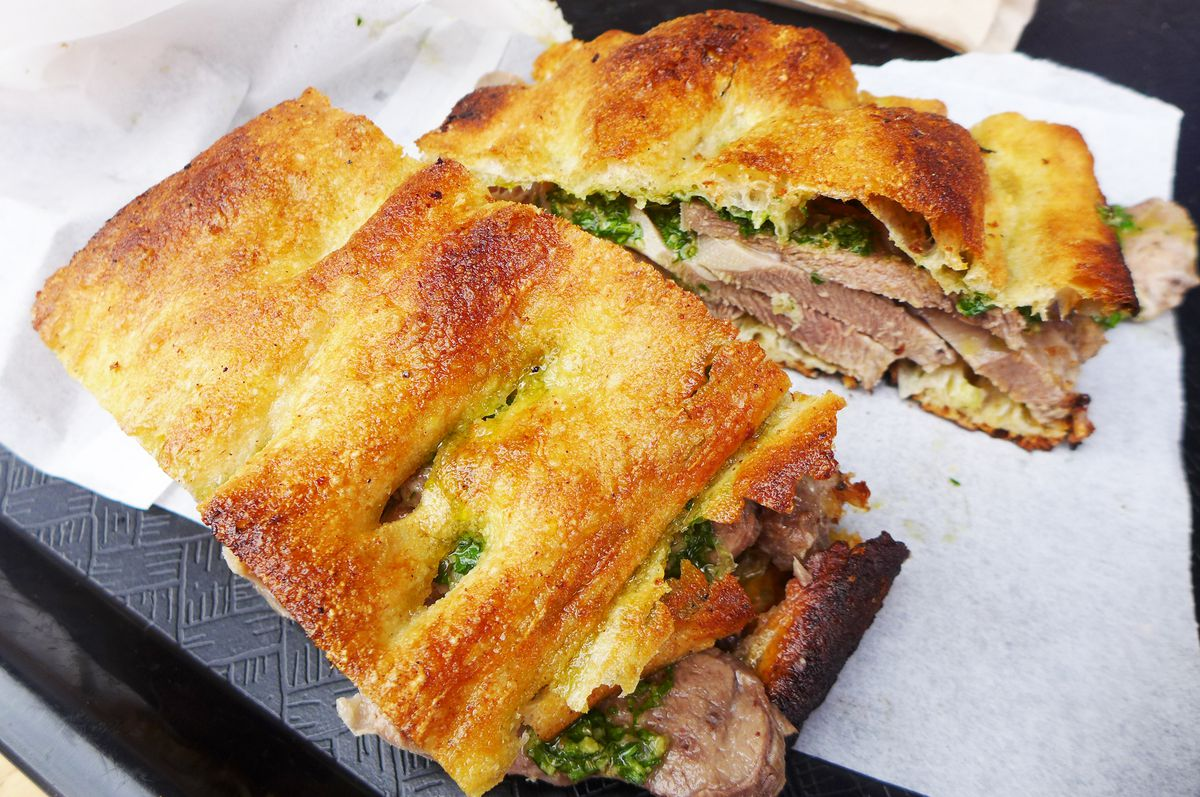 A sandwich on brown focaccia with meat and green sauce visible inside.