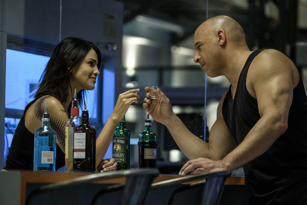 Vin Diesel, in a black sleeveless T-shirt, clinks shotglasses with Eiza Gonzalez, a dark-haired woman with an elaborate black tattoo of scales running down her left arm, in Bloodshot.