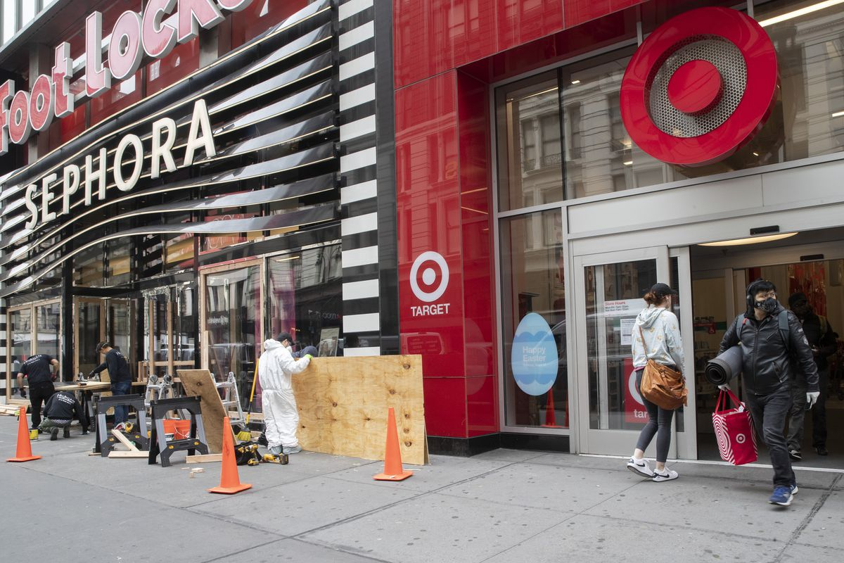 A shopper leaves the Target Store on 34th St. with supplies as carpenter board up the Sephora story, Friday, March 20, 2020, in New York.