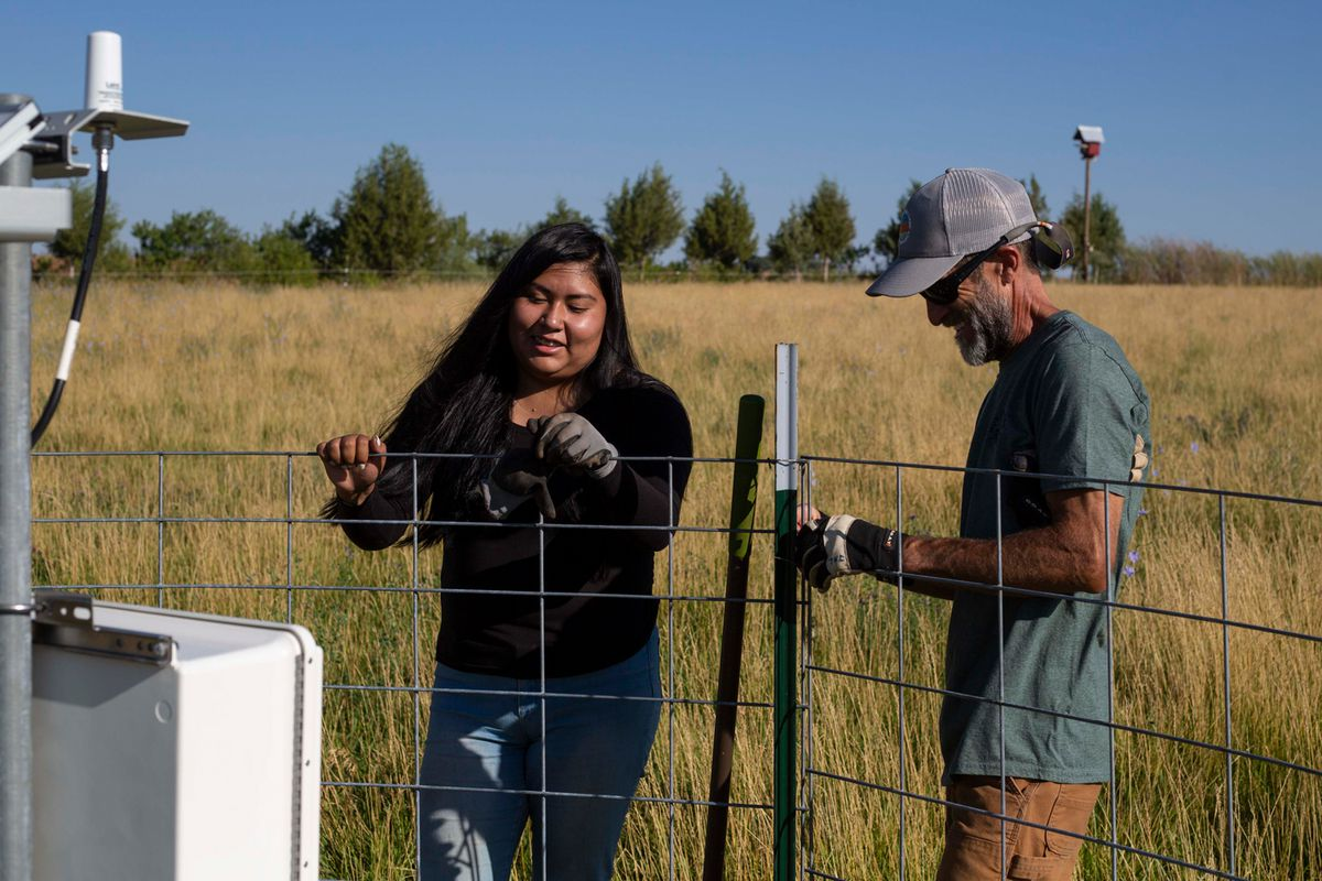 Marissa Moore and educator Jay Loschert stand near an irrigation system in a field.
