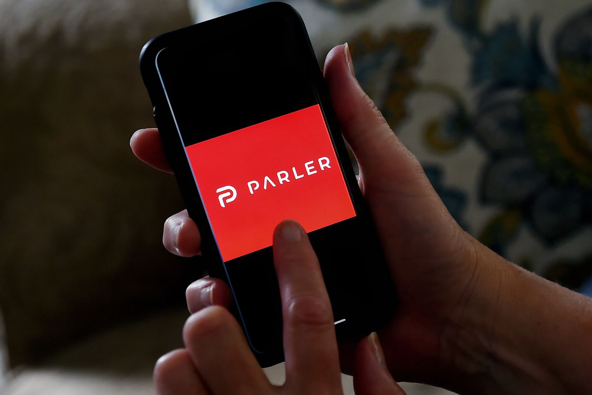 A person holds a smartphone and points to the logo for Parler on the screen.