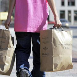 FILE - In this March 12, 2012 file photo, a shopper carries bags of merchandise in Freeport, Maine. U.S. retail sales rose at a solid pace in March 2012, as a healthier job market encouraged more consumers to shop, the Commerce Department said Monday, April 16, 2012.