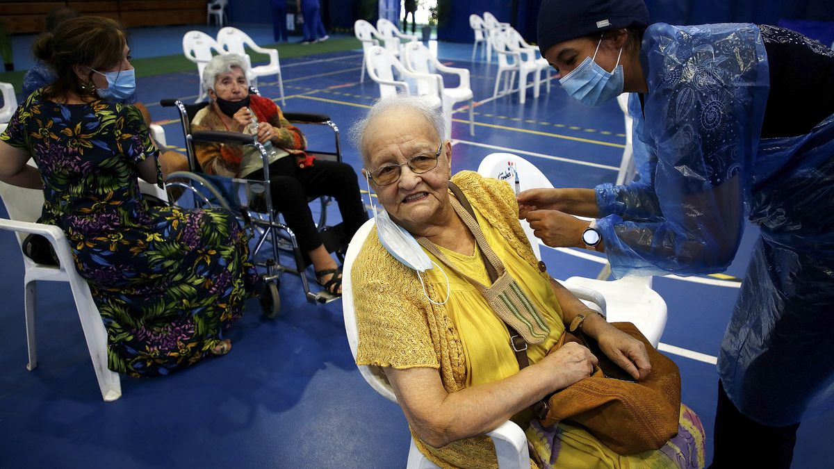 An older person sits while receiving a vaccine.