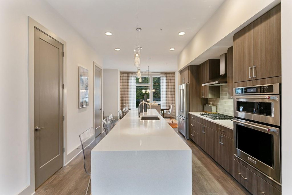 A long kitchen with a white island and wood cabinets and white walls.