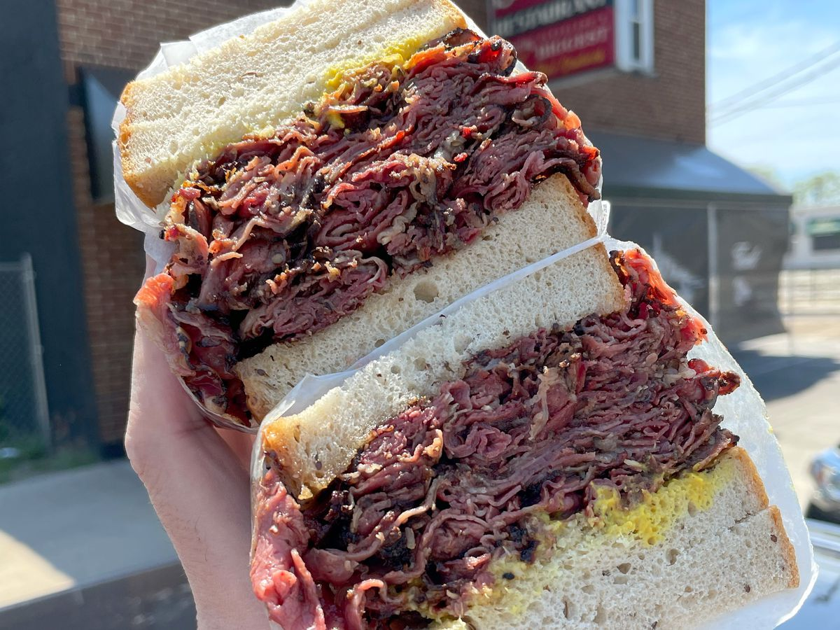 A hand holds two huge halves of a corned beef sandwich wrapped in butcher paper in front of a blurred restaurant exterior