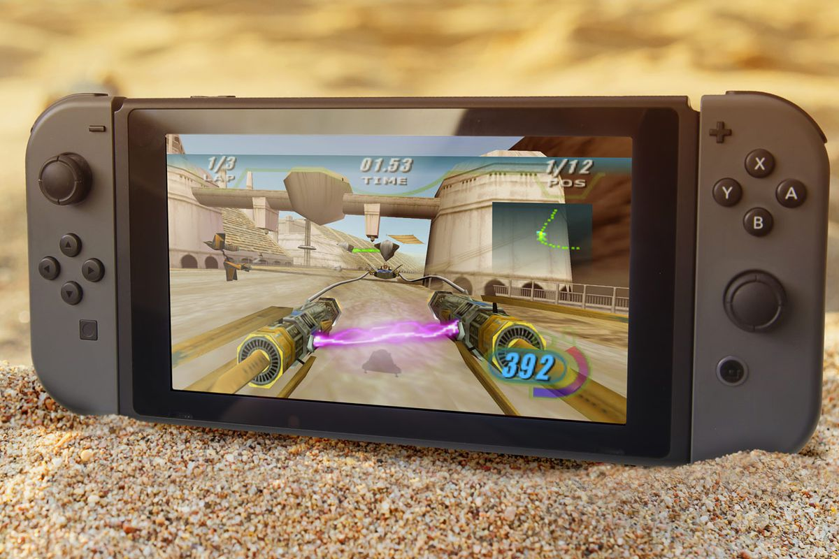 A photo of a Nintendo Switch playing Star Wars: Episode I Racer standing upright in sand