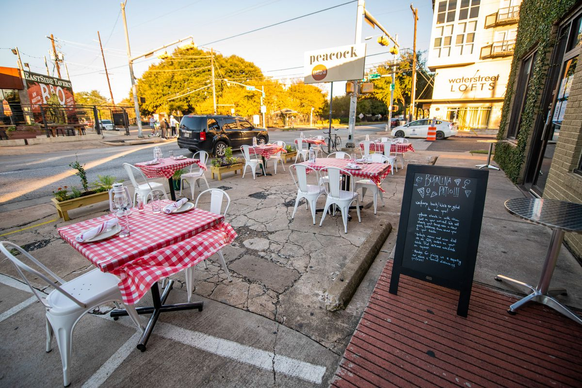 Another shot of the outdoor dining area with red and white table clothes and a sandwich sign in the foreground.