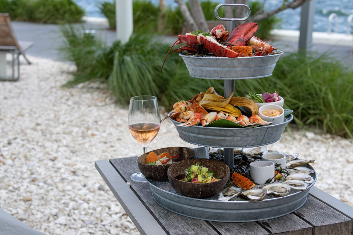 three level platter filled with various seafood, sitting on table outside