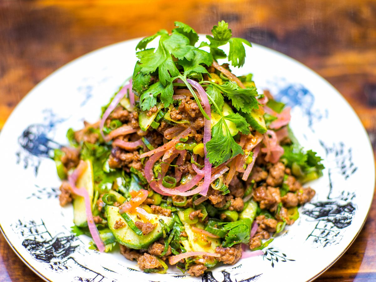 Lamb salad with red onions and cilantro on a blue patterned white plate