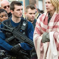A police officer stands guard as people are evacuated from Brussels airport, after explosions rocked the facility in Brussels, Belgium, Tuesday March 22, 2016. Authorities locked down the Belgian capital on Tuesday after explosions rocked the Brussels airport and subway system, killing  a number of people and injuring many more. Belgium raised its terror alert to its highest level, diverting arriving planes and trains and ordering people to stay where they were. Airports across Europe tightened security.