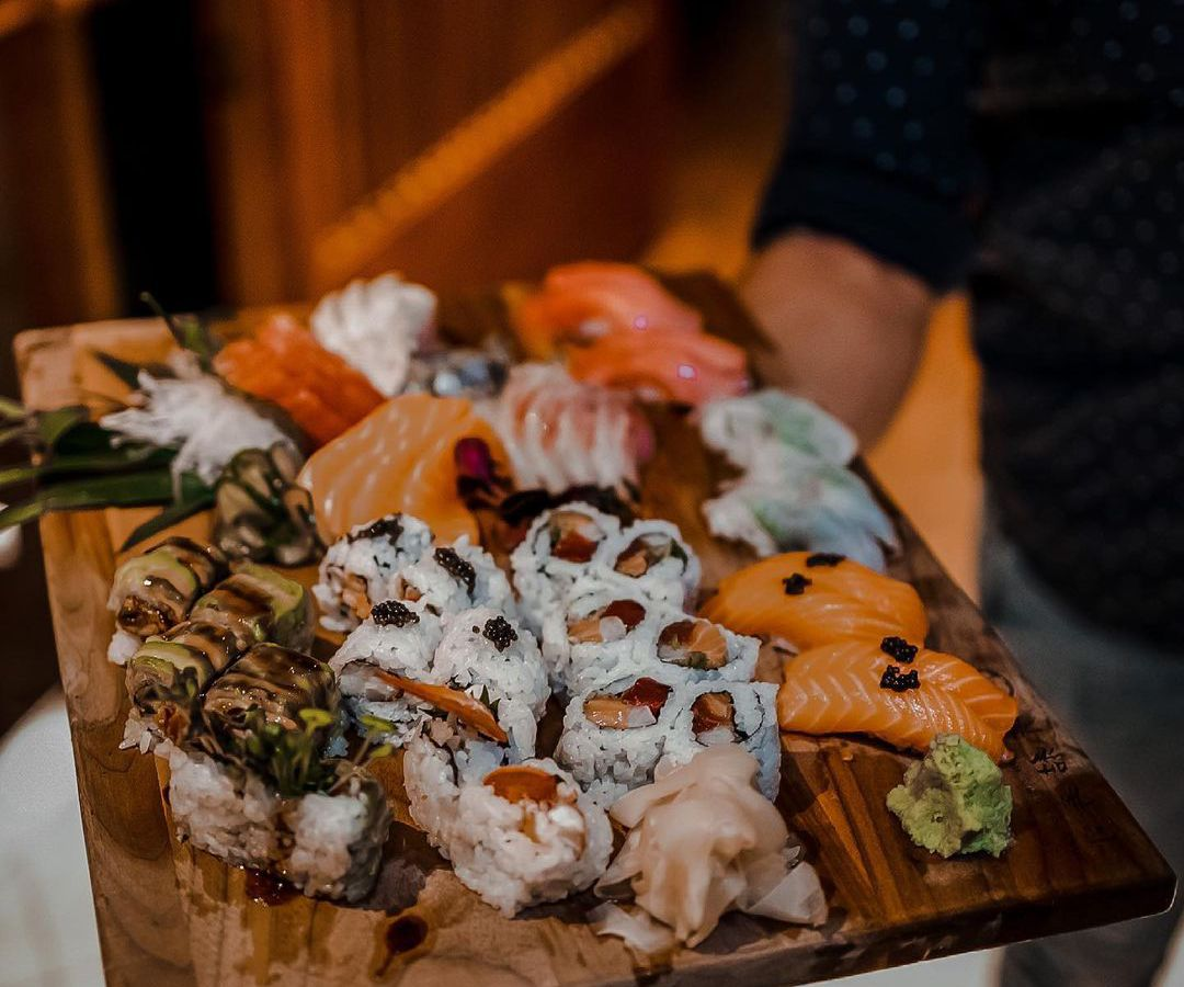 chopping board covered with fresh sushi