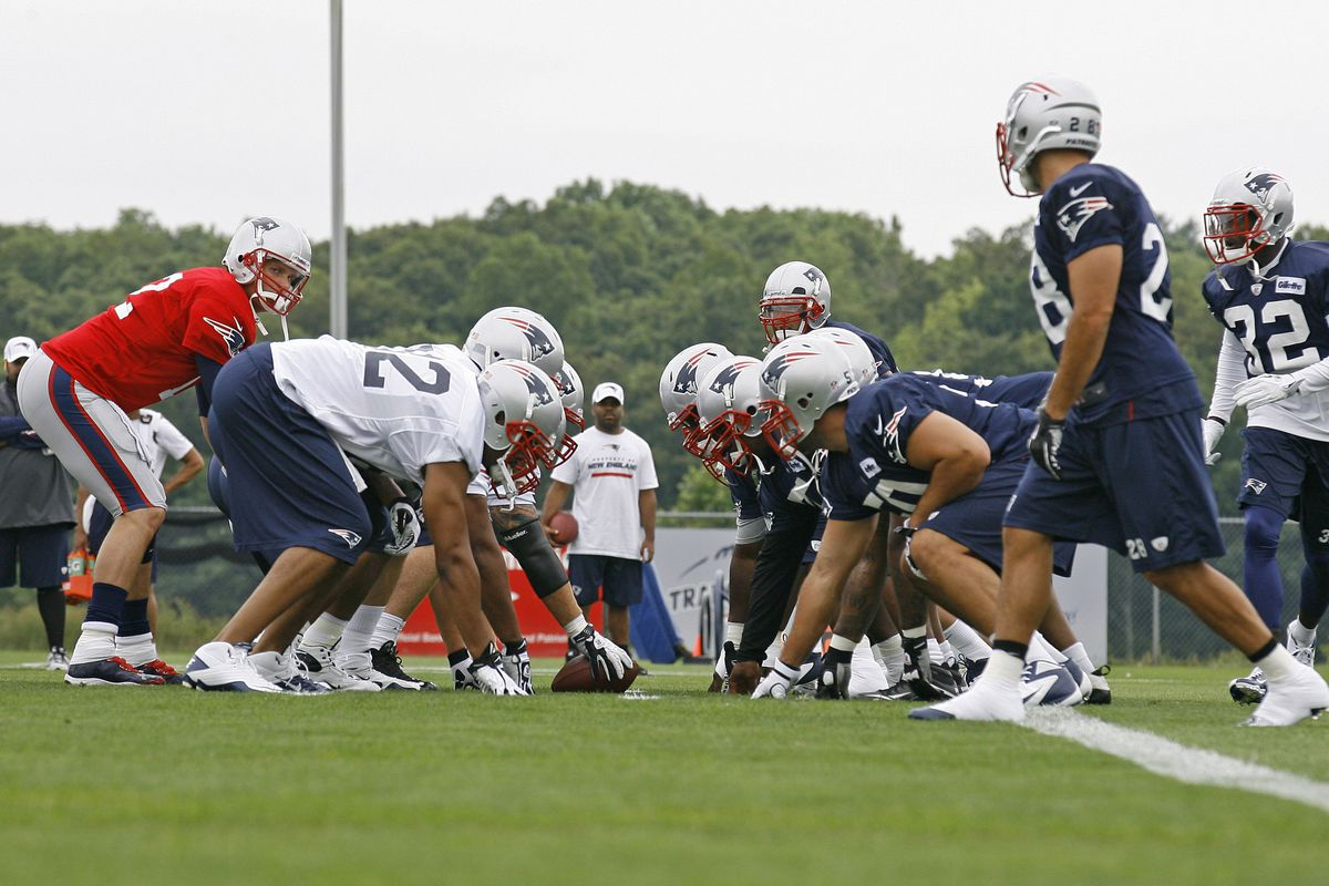 New England Patriots quarterback Tom Brady (red) lines up the offense against the defense during the Patriots opening day of training camp at the team practice facility.
